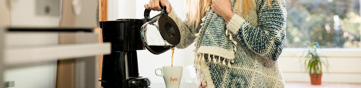 Frau mit frischen Kaffe aus der Kaffeemaschine
